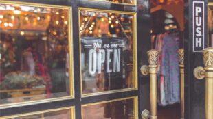 Enseigne ouverte accrochée à la vitrine de la boutique