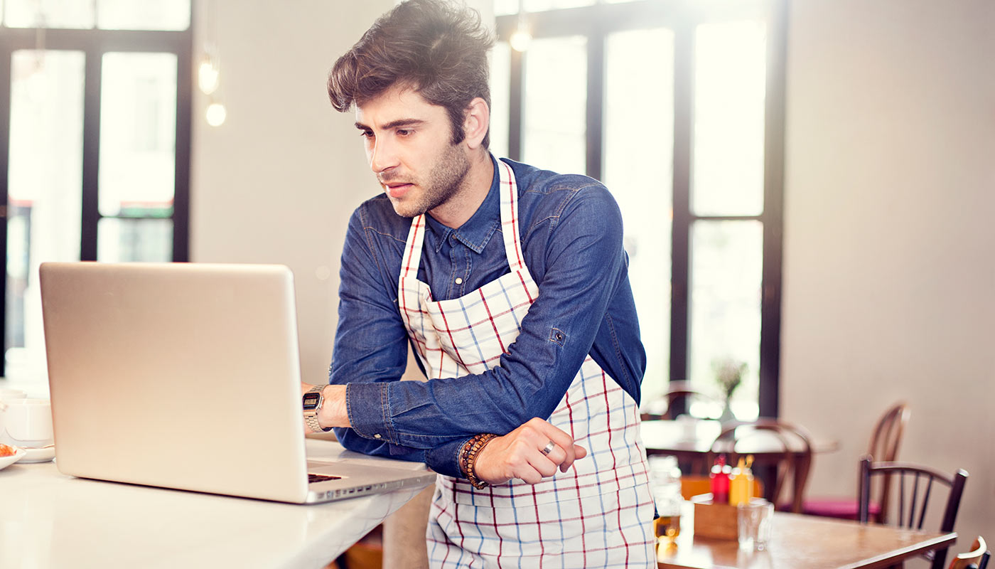 Restaurant server looking at laptop