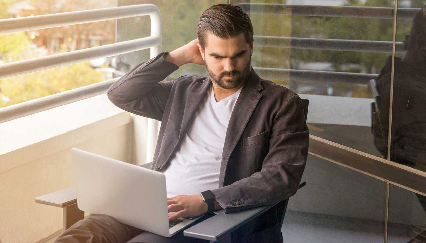 Man looking at laptop on balcony
