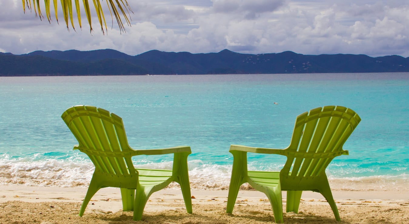 Green adirondack chairs on beach