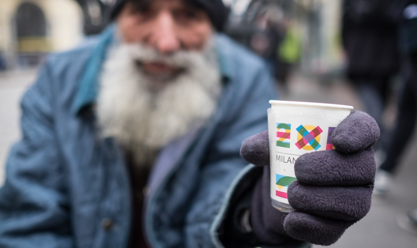 Homeless man holding change cup