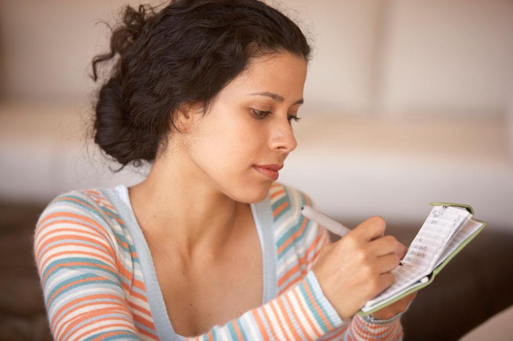 Woman writing in checkbook