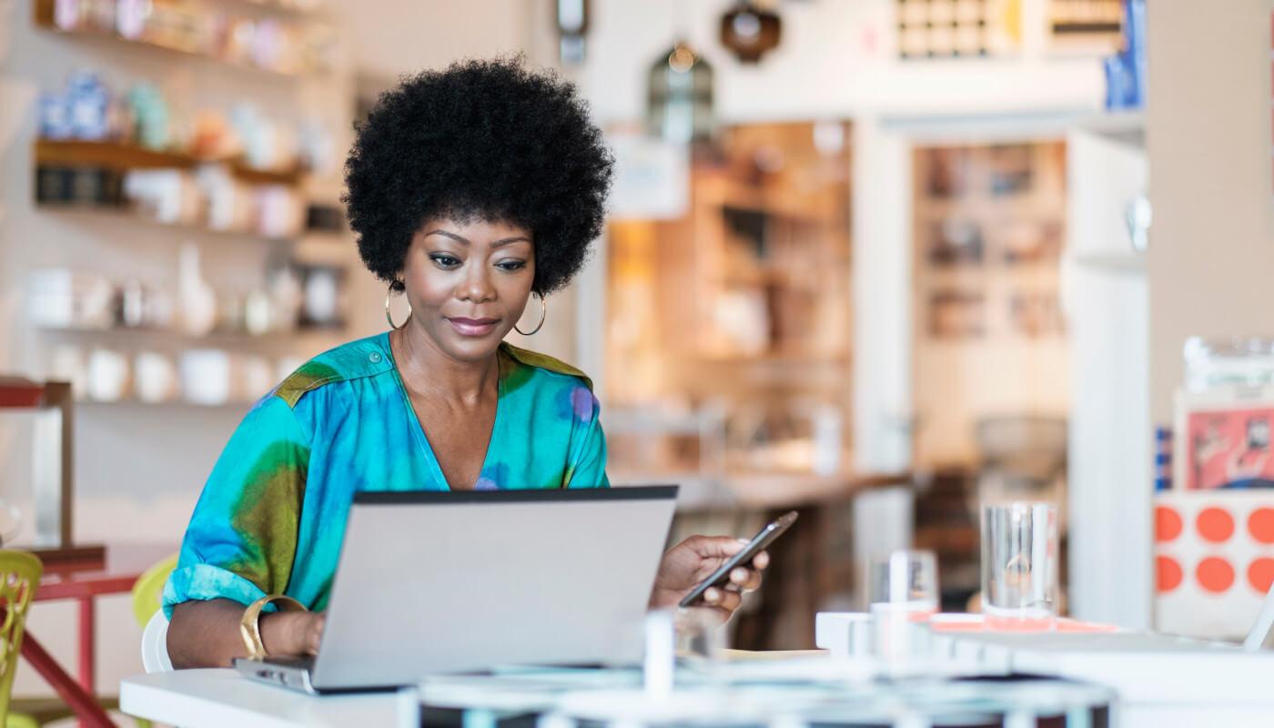 Woman on laptop in shop