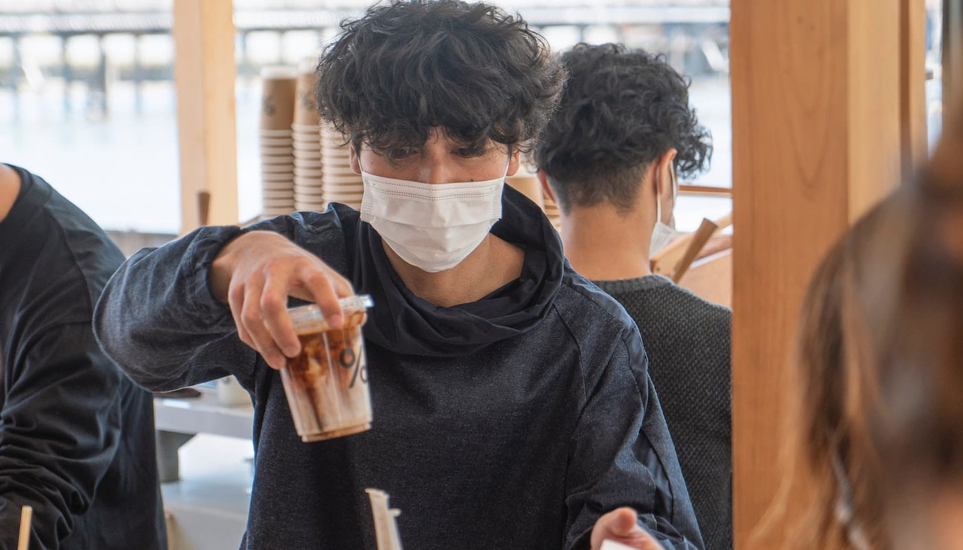 Masked cafe worker holding coffee drink