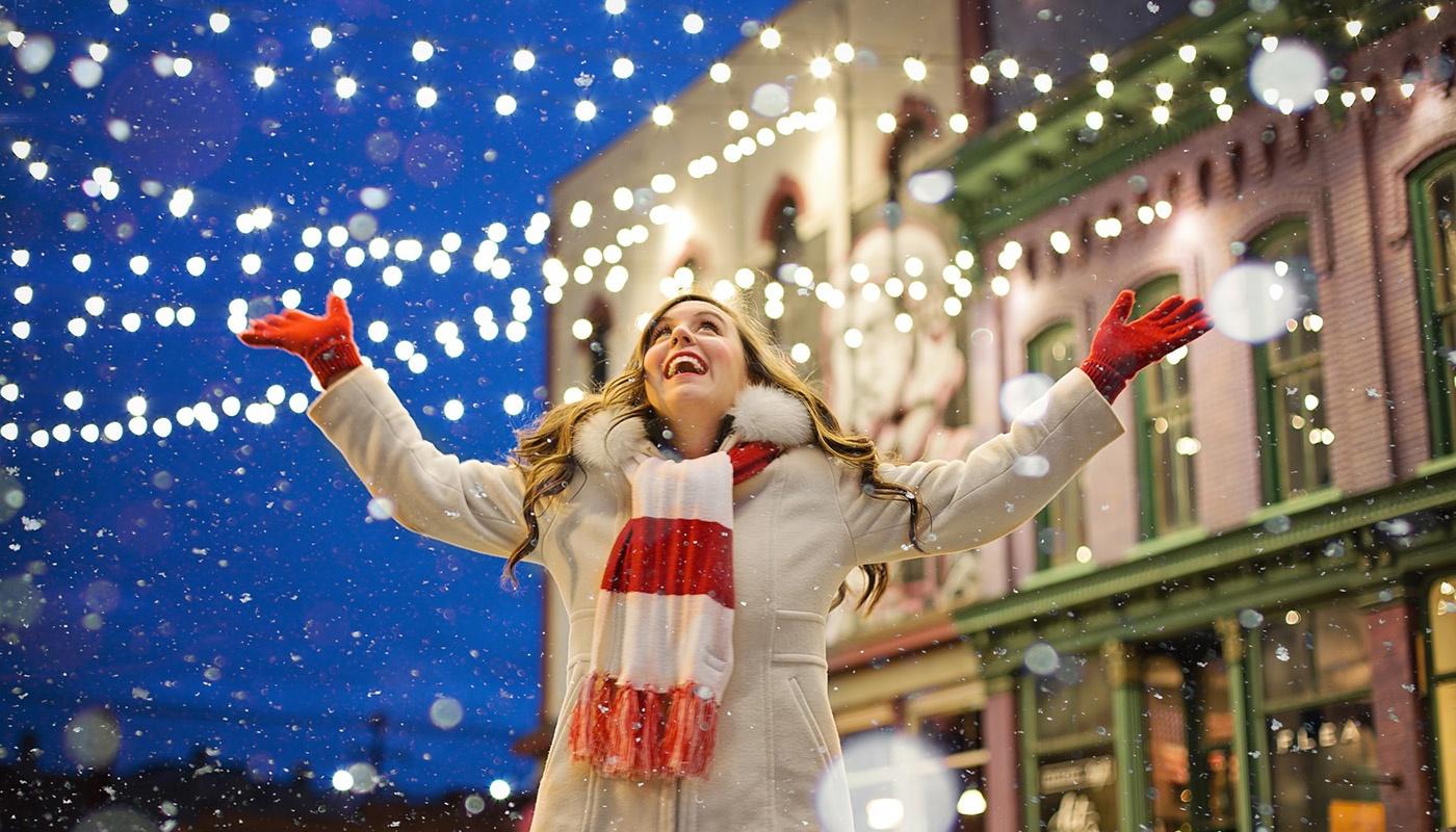 Woman raising arms during snowfall