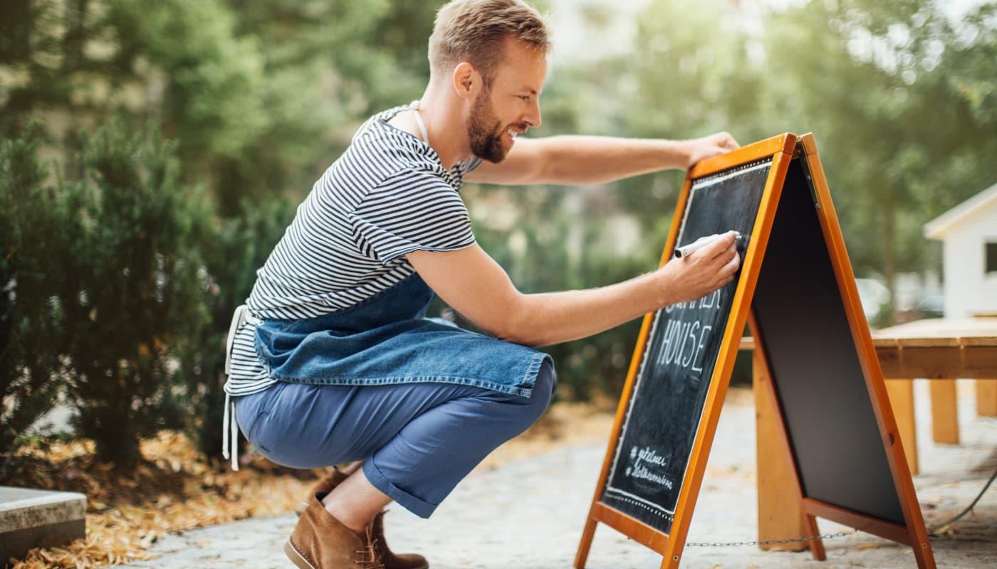 Restaurant owner writing on sidewalk sign