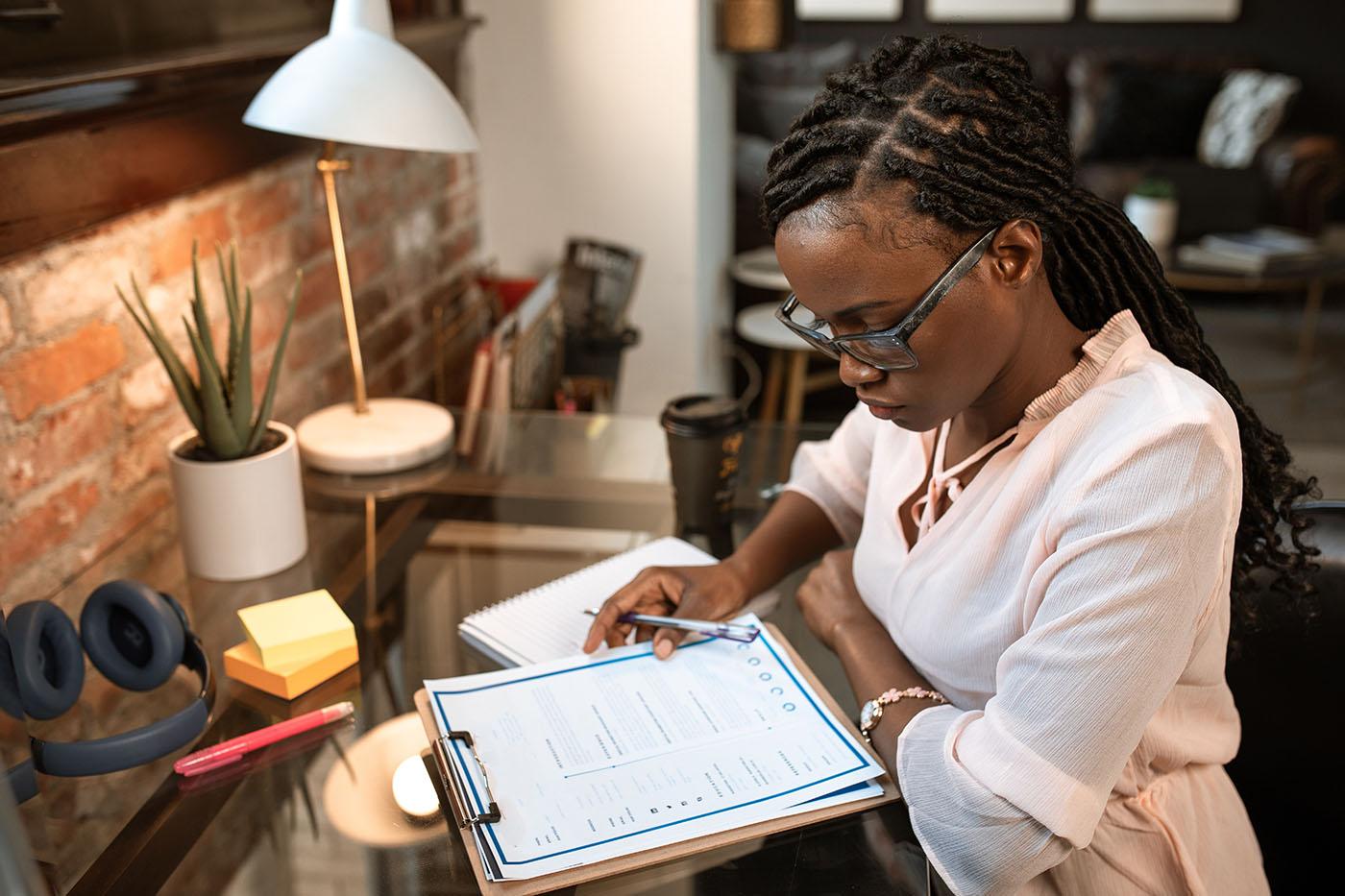 Black woman looking at clipboard