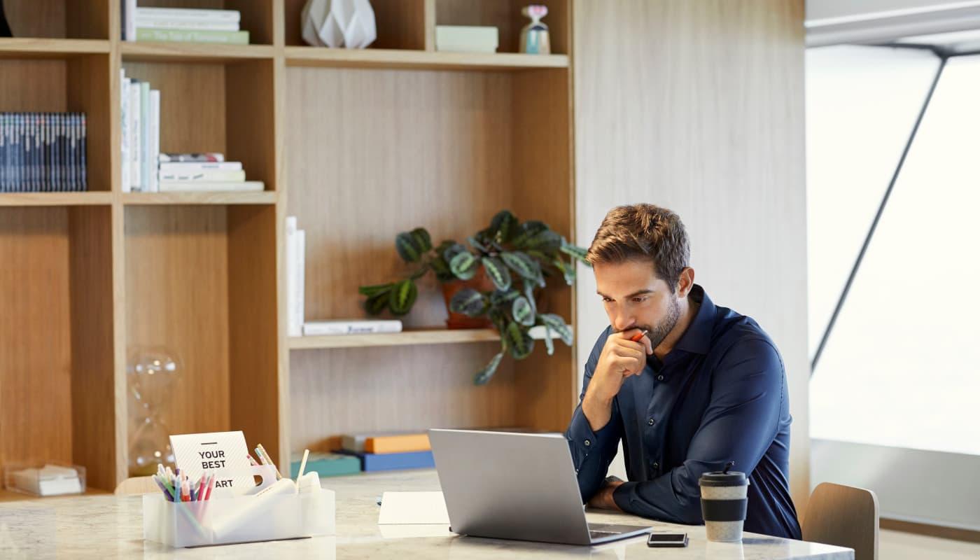 Man looking contemplative at laptop