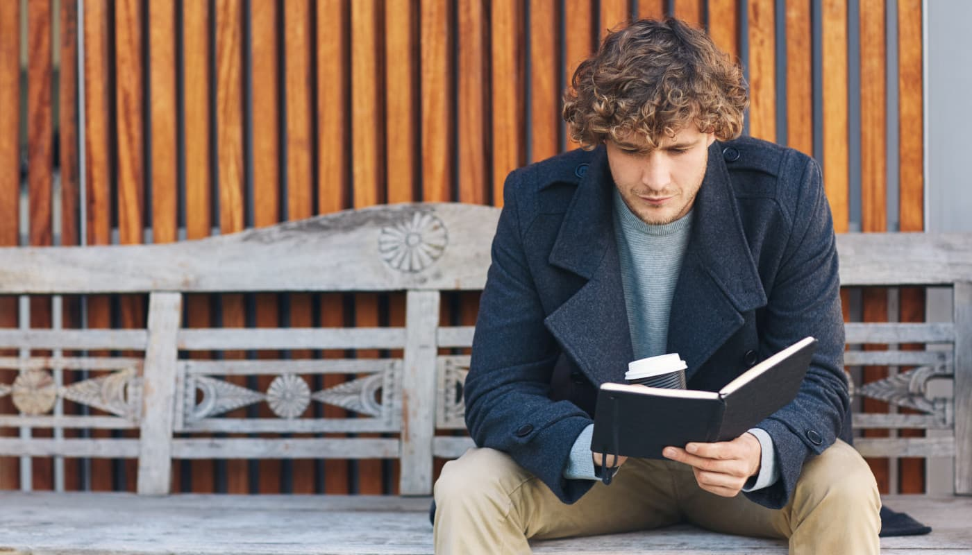 Man reading a book on a bench