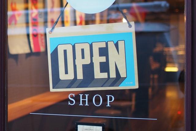 Open sign hanging in shop window