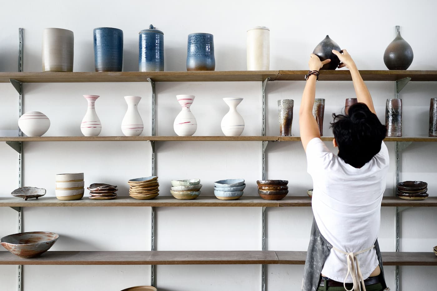 Store owner stocking pottery