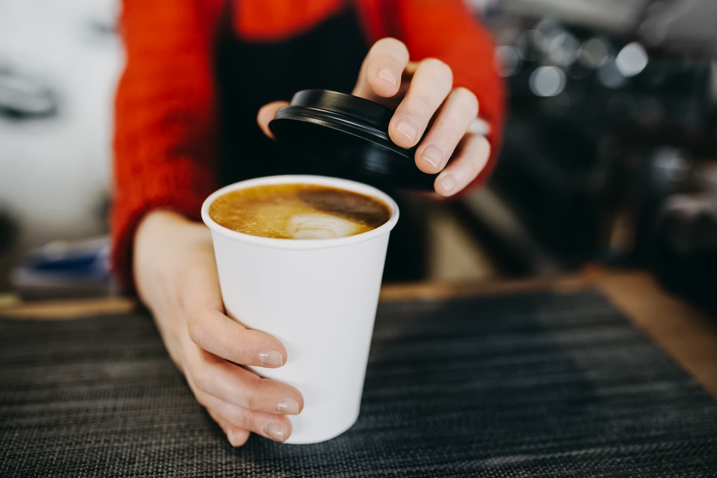 Barista putting lid on coffee cup